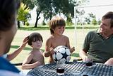 Boys with football and adults with wine
