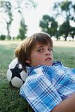 Boy lying on football