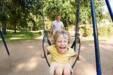 Father pushing boy on swing