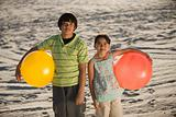 Brother and sister with beachballs