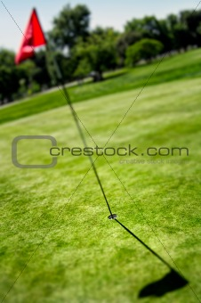 Flag and hole on golf field