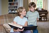 Boy and grandmother looking at book