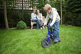 Boy riding bicycle in garden