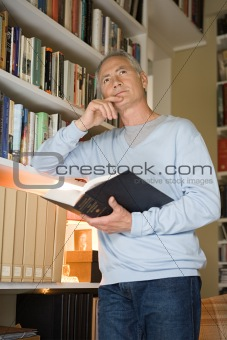 Man holding a book and thinking