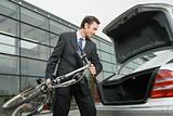 Businessman putting bicycle in car boot