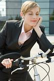 Businesswoman with earphones on bike