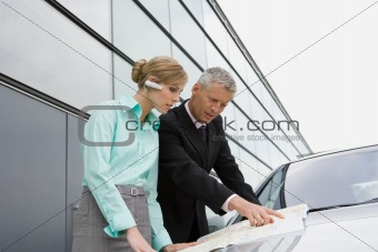 Businesswoman and businessman looking at map on automobile hood