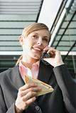 Businesswoman talking on mobile phone, holding sandwich