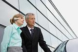 Businesswoman and businessman standing at car