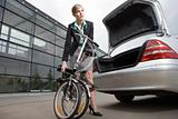 Businesswoman putting folded bicycle in car boot