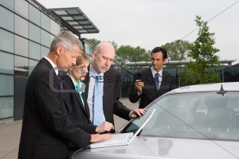 Businesspeople looking at laptop on automobile boot