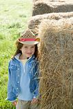 Girl standing at hay bale