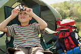 Boy sitting in front of tent, looking through binoculars