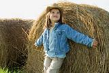 Girl standing against hay bale