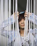 Young man behind metal bars