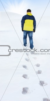 Man in yellow jacket walking on snow, footprints in snow, behind