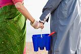 Indian couple carrying bucket and spade