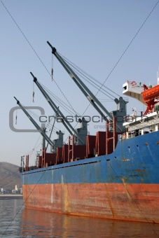 three cargo ship cranes