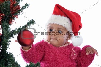 baby girl playing with christmas tree