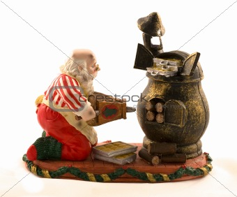 A cute decoration of santa baking cookies on a vintage stove