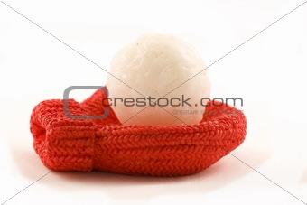 A red mitten holding a snowball