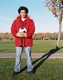 Man holding a football in park