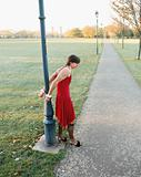 Man handcuffed to lamp post wearing red dress