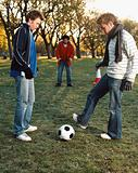 Men playing football in park