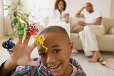 Boy in living room playing with monster finger puppets