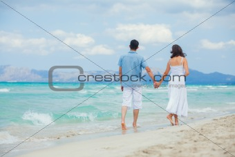 Happy young couple walking on a tropical beach