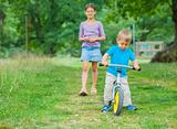 Little boy on a bicycle and his sister