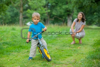 Little boy on a bicycle and his mother