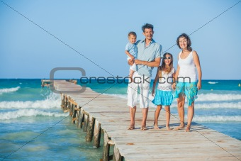 Family of four on jetty by the ocean