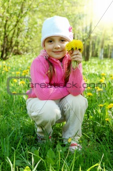 Little girl is smelling dandelion in the field
