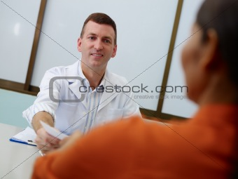 Gynecologist working and talking to woman in clinic