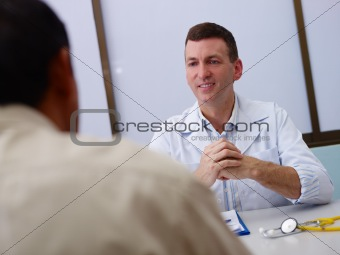 Doctor working and talking to old sick man in clinic