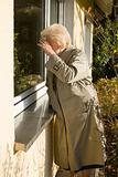 Senior woman looking through window