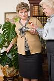 Senior woman pouring tea into flower pot