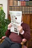 Senior man looking through a hole in a newspaper
