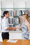 Colleagues shaking hands near bookshelf