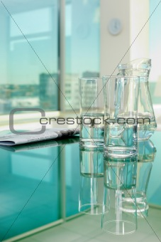 Water and newspaper on table
