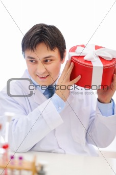 Happy medical doctor shaking present box trying to guess whats inside