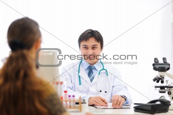 Medical doctor speaking with patient at office