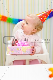 Baby with present looking in corner