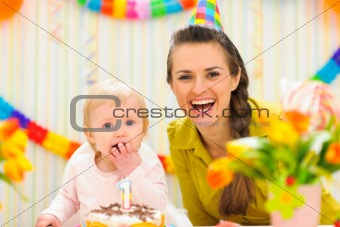 Portrait of mother with baby eating birthday cake