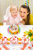 Portrait of happy mom and baby with birthday cake