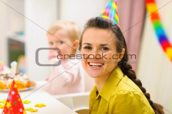 Portrait of mother and baby eating birthday cake in background