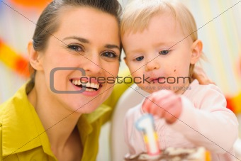 Portrait of mom and baby eating birthday cake