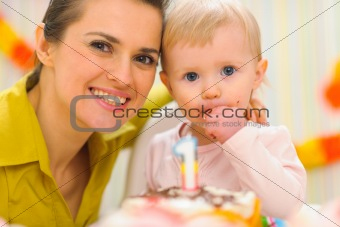 Portrait of mother and kid eating birthday cake