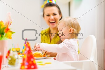 Baby celebrating first birthday with mother
